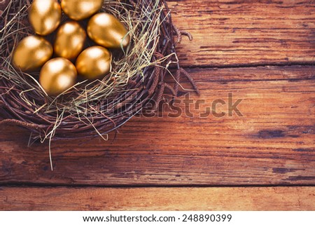 Gold eggs in nest from hay on wood boards with copyspace - stock photo