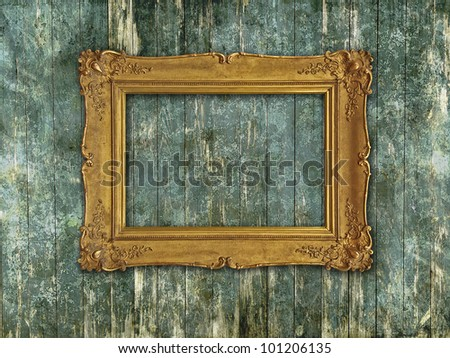 Gold empty baroque frame on a scratched grunge green wood plank wall