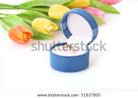 Gold  engagement ring in box on the flowers background - stock photo