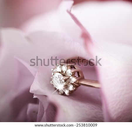 gold engagement ring with diamonds in beautiful rose flower, macro view and copy space - stock photo