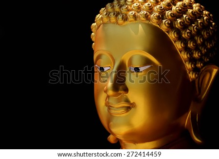 Gold face Buddha statue on black background.
