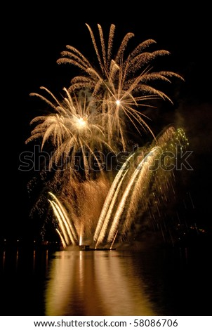 Gold fireworks with lake reflection.