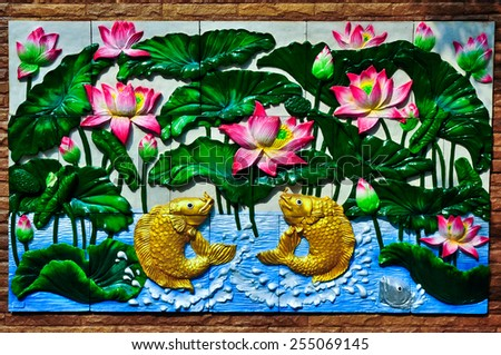 Gold fishes and lotus Thai stucco on the temple wall - stock photo