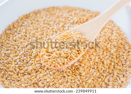 Gold flax seeds on a wooden spoon, stock photo - stock photo