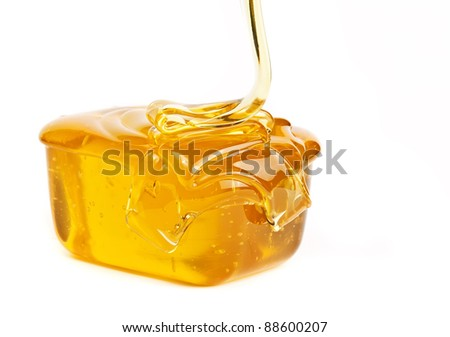 Gold flowing honey isolated on white background