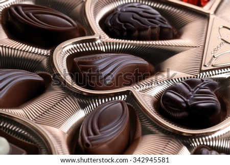 Gold foil box of assorted chocolates background - stock photo