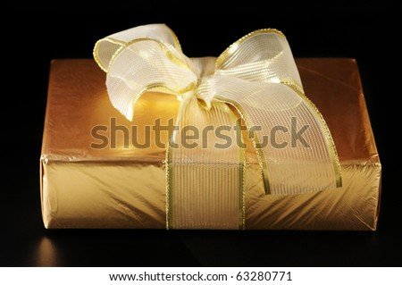 Gold foil gift with golden bow on black background. - stock photo