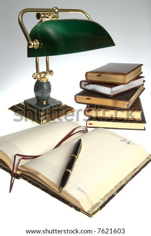 Gold fountain pen on a notebook under a lamp - stock photo
