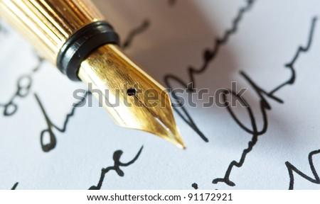 Gold fountain pen on hand written letter - stock photo