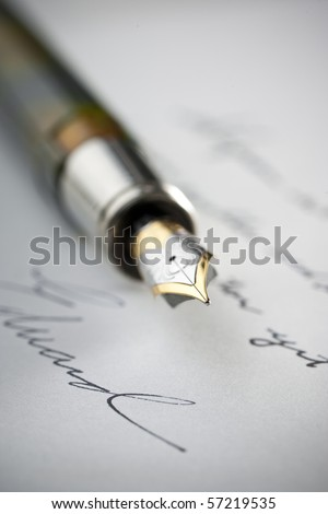 Gold fountain pen on hand written letter with selective focus on tip of pen nib. - stock photo