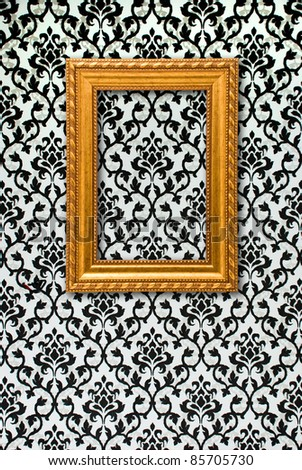 Gold frame on a black and white wallpaper - stock photo