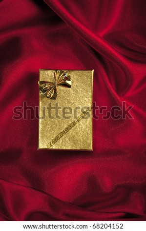Gold gift box an a smooth red satin