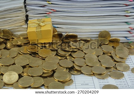 Gold gift box in heap of gold coins with pile of paperwork.                                - stock photo
