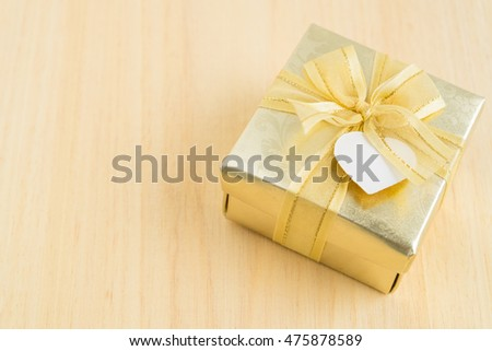Gold gift box on wooden background. Golden present object on wooden table.