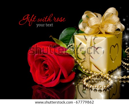Gold gift with red rose on black background. Copy-space - stock photo