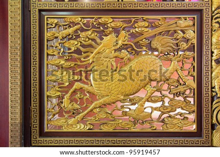 Gold Gilt Wood Carving of Qilin on Chinese Temple Wall in Chinatown - stock photo