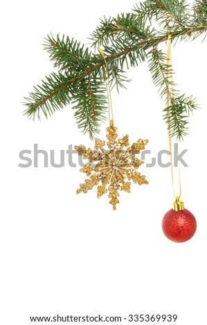 Gold glitter Christmas star ornament and red bauble hanging from a conifer branch against a white background - stock photo
