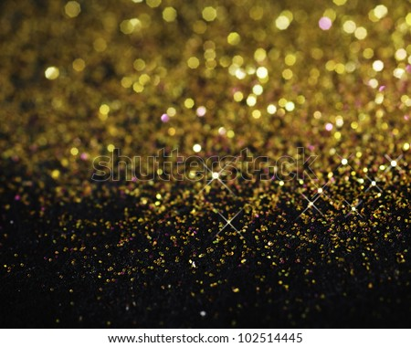 Gold glitter on black background with selective focus - stock photo
