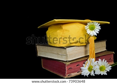 gold graduation cap and daisies on old books