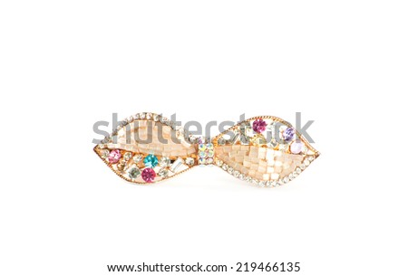 Gold hair clip with decorative stones on a white background