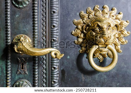 gold handle and knocker with lion - stock photo