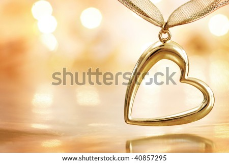 Gold heart pendant hanging over golden reflective background with defocused lights. Shallow DOF. - stock photo