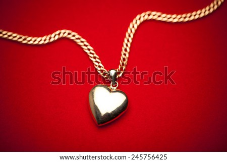 gold heart pendant on red background - stock photo