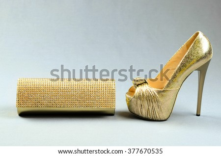 Gold high-heeled shoe and clutch bag on a gray background - stock photo