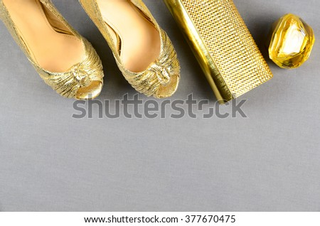 Gold high-heeled shoes, clutch bag and perfume on a gray background. Top view - stock photo