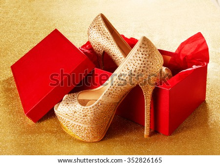 Gold high heels with red shoes box. on the golden paper background. Christmas present, Valentine gift. Shopping - stock photo
