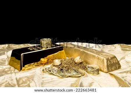 Gold in various forms including dust, nuggets, bar, ingot and coins isolated on a black background for placement of copy