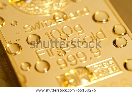 gold ingot and water drops background. closeup. - stock photo