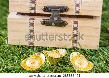 gold ingot and wood coffer on grass background - stock photo