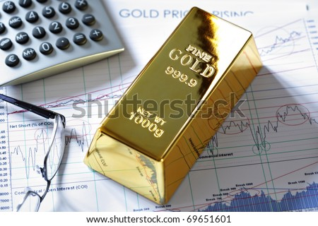Gold ingot resting on a stocks and shares graph representing investment or banking - stock photo