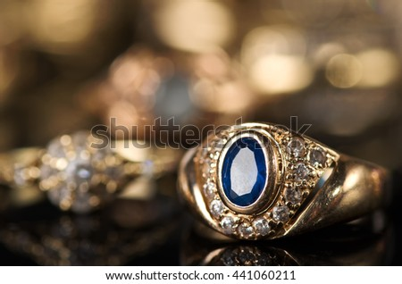 Gold jewelry on a black background. - stock photo