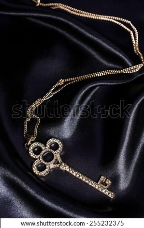 gold key pendant on black silk - stock photo