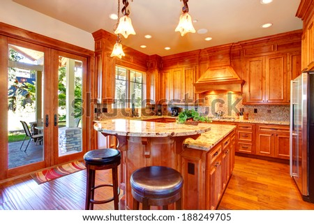 Gold kitchen room with cabinets, back splash trim and kitchen island. Room has door to the backyard deck - stock photo