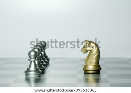Gold Knight in front of Silver Pawns on chess game - stock photo
