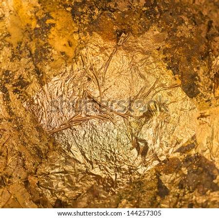 Gold leaf on the wall background - stock photo