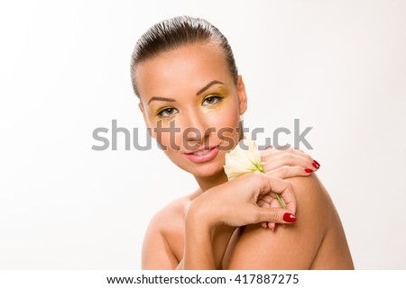 Gold make up. Brown sleek hair beautiful woman with white flower in hands close to face.