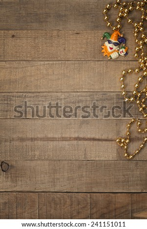 Gold Mardi Gras Beads with Court Jester on Rustic Brown Wood Background with room or space for copy, text, your words.  Above looking down vertical - stock photo