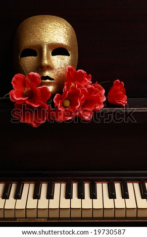 gold mask and red flower on a piano - stock photo