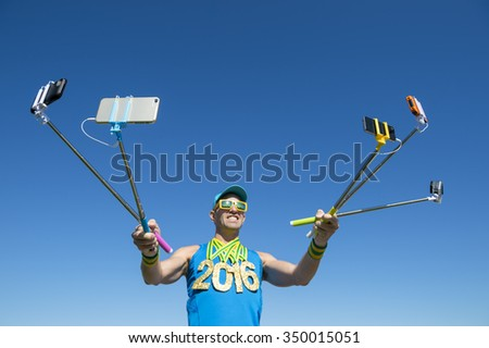 Gold medal 2016 athlete making a face for his many gadgets on selfie sticks as he poses for photos - stock photo