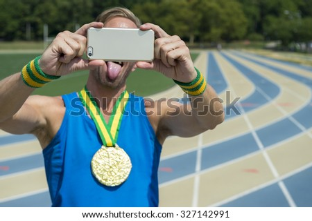 Gold medal athlete making faces at his mobile phone taking a selfie at running track  - stock photo
