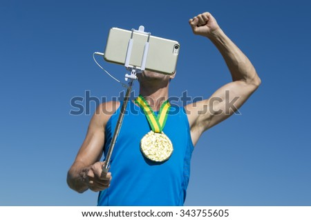Gold medal athlete punching the air for a selfie with a mobile phone on a selfie stick - stock photo