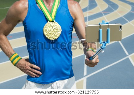Gold medal athlete standing at running track taking a selfie on his mobile phone with selfie stick - stock photo