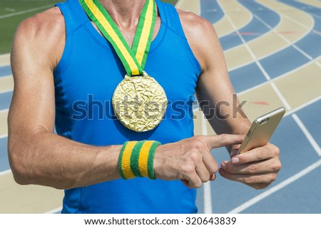 Gold medal athlete standing at running track using his mobile phone - stock photo