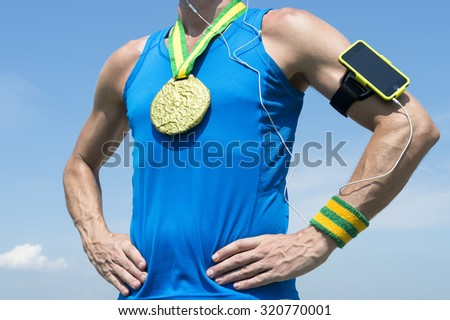 Gold medal athlete standing with mobile phone armband and headphones against blue sky - stock photo