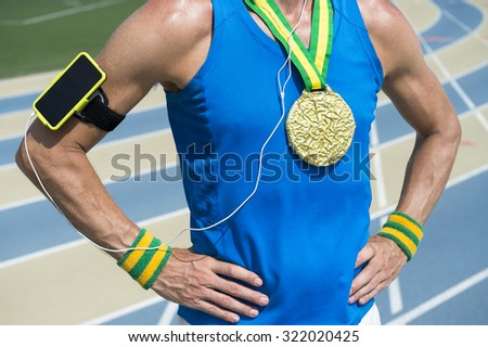 Gold medal athlete standing with mobile phone armband and headphones against running track background - stock photo