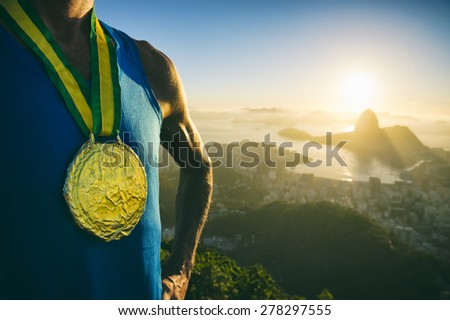 Gold medal champion athlete standing outdoors at the golden sunrise at Rio de Janeiro skyline - stock photo